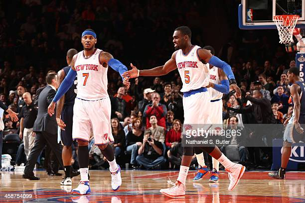 Teammates Carmelo Anthony of the New York Knicks and Tim Hardaway Jr #5 of the New York Knicks high five during a game against the Memphis Grizzlies...