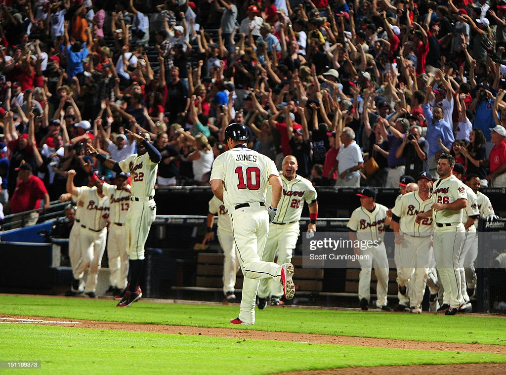Teammates celebrate as <a gi-track='captionPersonalityLinkClicked' href=/galleries/search?phrase=Chipper+Jones&family=editorial&specificpeople=171256 ng-click='$event.stopPropagation()'>Chipper Jones</a> #10 of the Atlanta Braves runs the bases after hitting a three-run walk-off home run against the Philadelphia Phillies at Turner Field on September 2 2012 in Atlanta, Georgia.