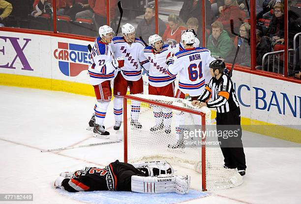 Teammates celebrate with Derek Stepan of the New York Rangers after his gamewinning goal against Anton Khudobin of the Carolina Hurricanes during the...