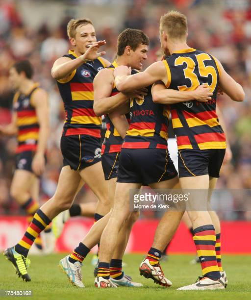Teammates celebrate with Luke Brown of the Crows after he kicked a goal during the round 19 AFL match between the Adelaide Crows and Port Adelaide...