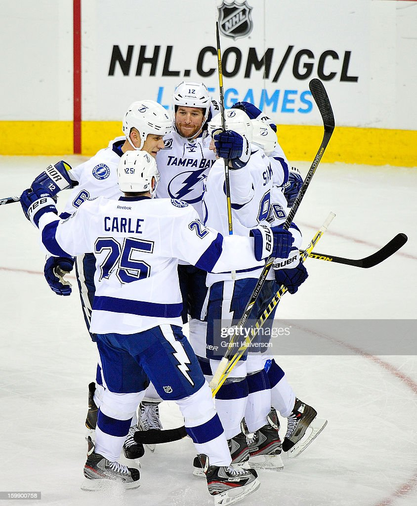 Teammates celebrate with Ryan Malone #12 of the Tampa Bay Lightning after his third period goal against the Carolina Hurricanes during play at PNC Arena on January 22, 2013 in Raleigh, North Carolina. Tampa Bay won 4-1.