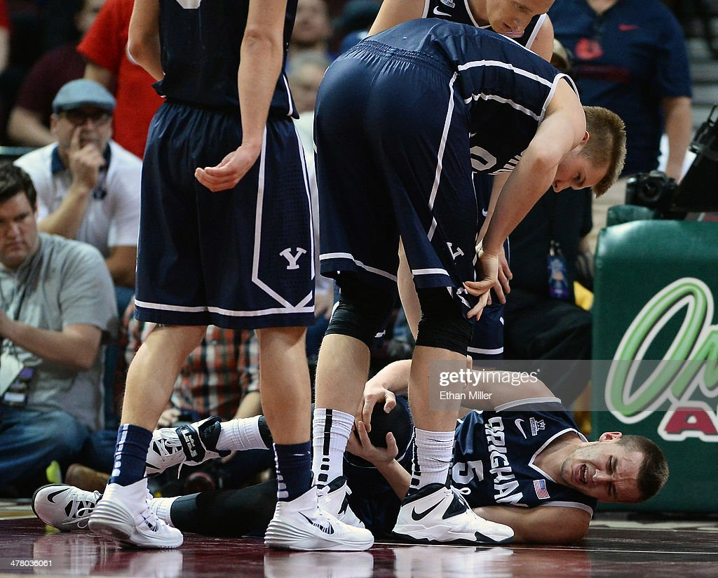 Teammates check on Kyle Collinsworth #5 of the Brigham Young Cougars as he holds his knee after injuring it during the championship game of the West Coast Conference Basketball tournament against the Gonzaga Bulldogs at the Orleans Arena on March 11, 2014 in Las Vegas, Nevada. Gonzaga won 75-64.