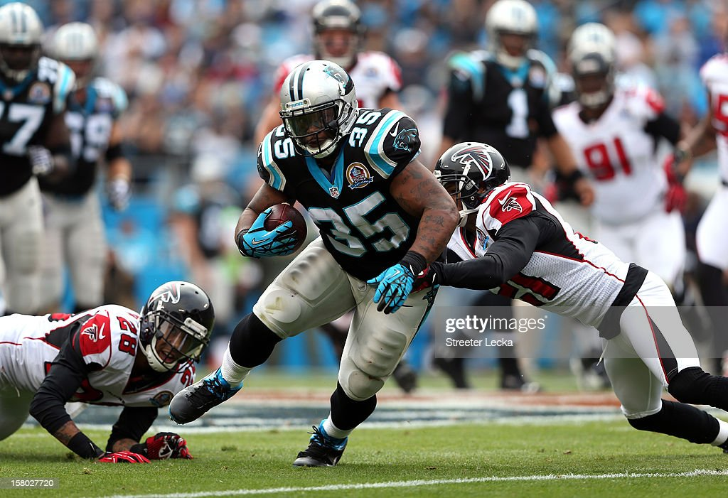 Teammates Chris Owens #21 of the Atlanta Falcons and Thomas DeCoud #28 tackle Mike Tolbert #35 of the Carolina Panthers during their game at Bank of America Stadium on December 9, 2012 in Charlotte, North Carolina.