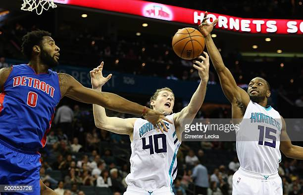 Teammates Cody Zeller and Kemba Walker of the Charlotte Hornets go after a loose ball against Andre Drummond of the Detroit Pistons during their game...