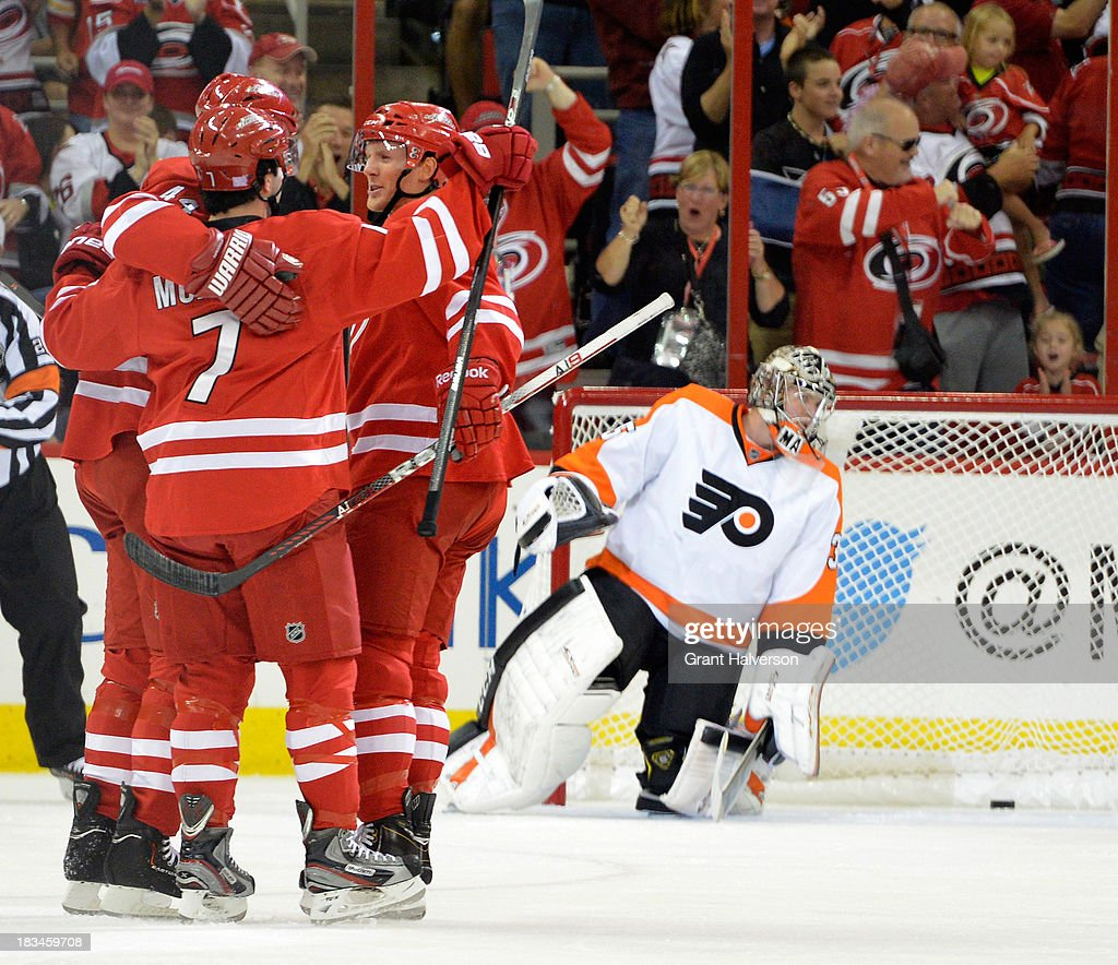 Teammates congratuate <a gi-track='captionPersonalityLinkClicked' href=/galleries/search?phrase=Jay+Harrison&family=editorial&specificpeople=714374 ng-click='$event.stopPropagation()'>Jay Harrison</a> #44 of the Carolina Hurricanes after his goal against Steve Mason #35 of the Philadelphia Flyers during the first period at PNC Arena on October 6, 2013 in Raleigh, North Carolina.
