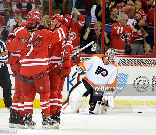 Teammates congratuate Jay Harrison of the Carolina Hurricanes after his goal against Steve Mason of the Philadelphia Flyers during the first period...