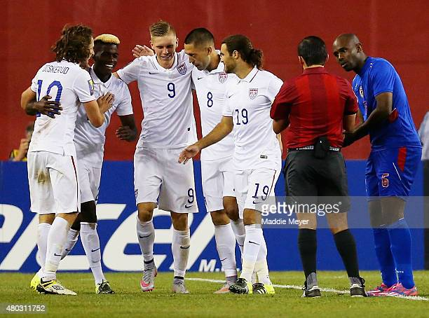 Teammates congratulate Clint Dempsey of United States after he scored a goal as Frantz Bertin of Haiti right disputes the call during the 2015...