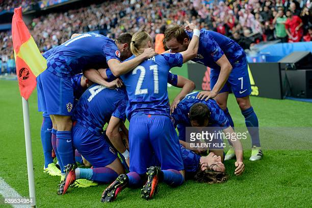 Teammates congratulate Croatia's midfielder Luka Modric as they celebrate the team's first goal during the Euro 2016 group D football match between...