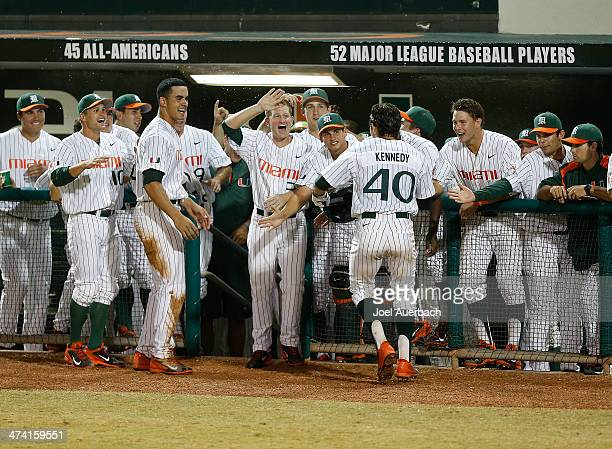 Teammates congratulate Garrett Kennedy of the Miami Hurricanes after he hit a sixth inning home run against the Florida Gators on February 21 2014 at...
