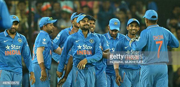 Teammates congratulate India's Virat Kohli for taking a catch to effect the dismissal of South Africa's Dale Steyn during the second one day...