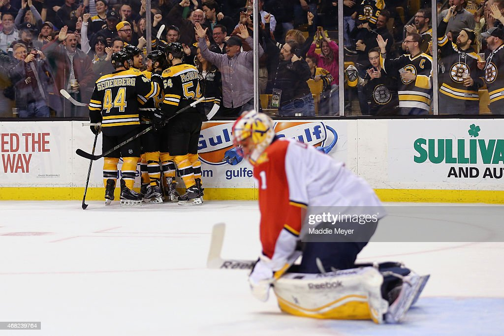 Teammates congratulate Milan Lucic of the Boston Bruins after he scored the game winning goal against Roberto Luongo of the Florida Panthers during...