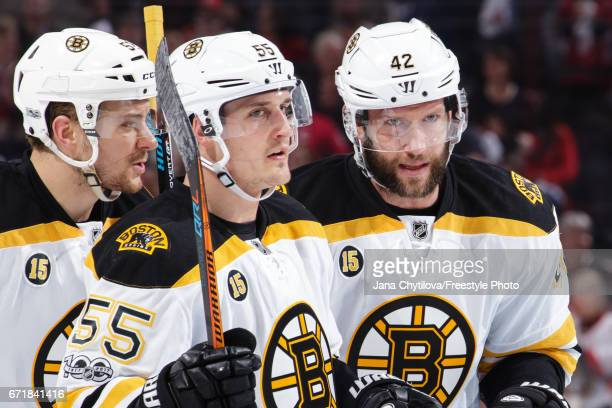 Teammates David Backes Noel Acciari and Sean Kuraly of the Boston Bruins chat during a stoppage in play against the Ottawa Senators in Game Five of...