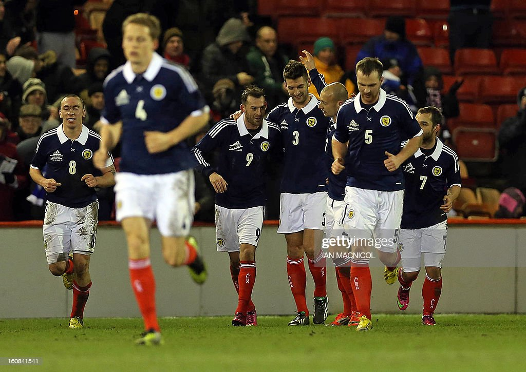 Teammates, defender Alan Hutton (3rd R) and striker Steven Fletcher (3rd L) congratulate Charlie Mulgrew (C) after he scores the opening goal of the international friendly football match between Scotland and Estonia at Pittodrie Stadium in Aberdeen, northeast Scotland, on February 6, 2013.