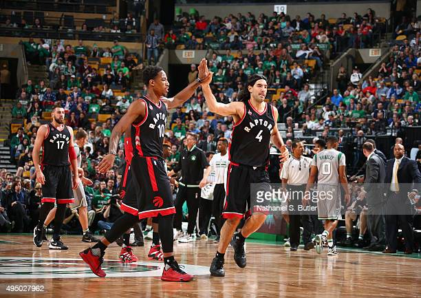 Teammates DeMar DeRozan and Luis Scola of the Toronto Raptors highfive during a game against the Boston Celtics on October 30 2015 at TD Garden in...