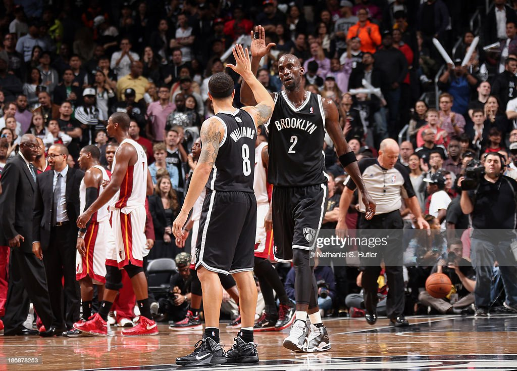 Teammates Deron Williams #8 of the Brooklyn Nets and Kevin Garnett #2 of the Brooklyn Nets high five after defeating the Miami Heat at Barclays Center on November 1, 2013 in the Brooklyn borough of New York City.