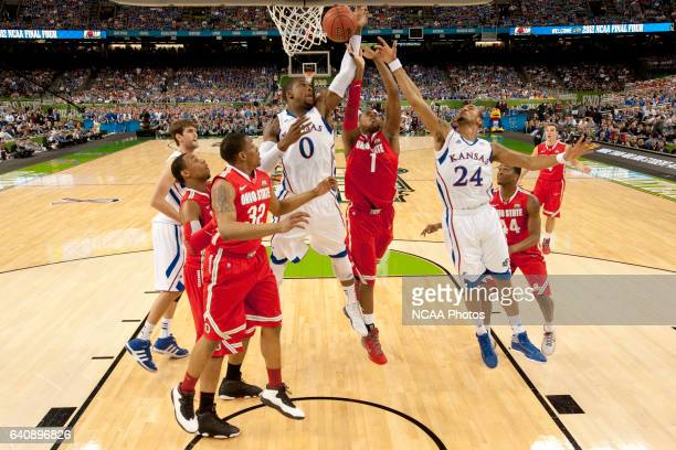 Teammates forward Thomas Robinson and guard Travis Releford from the University of Kansas battle for control of the ball against forward Deshaun...