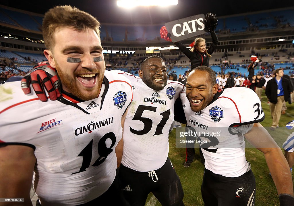 Teammates George Winn #32, Travis Kelce #18 and Greg Blair #51 of the Cincinnati Bearcats celebrate after defeating the Duke Blue Devils 48-34 during their game at Bank of America Stadium on December 27, 2012 in Charlotte, North Carolina.