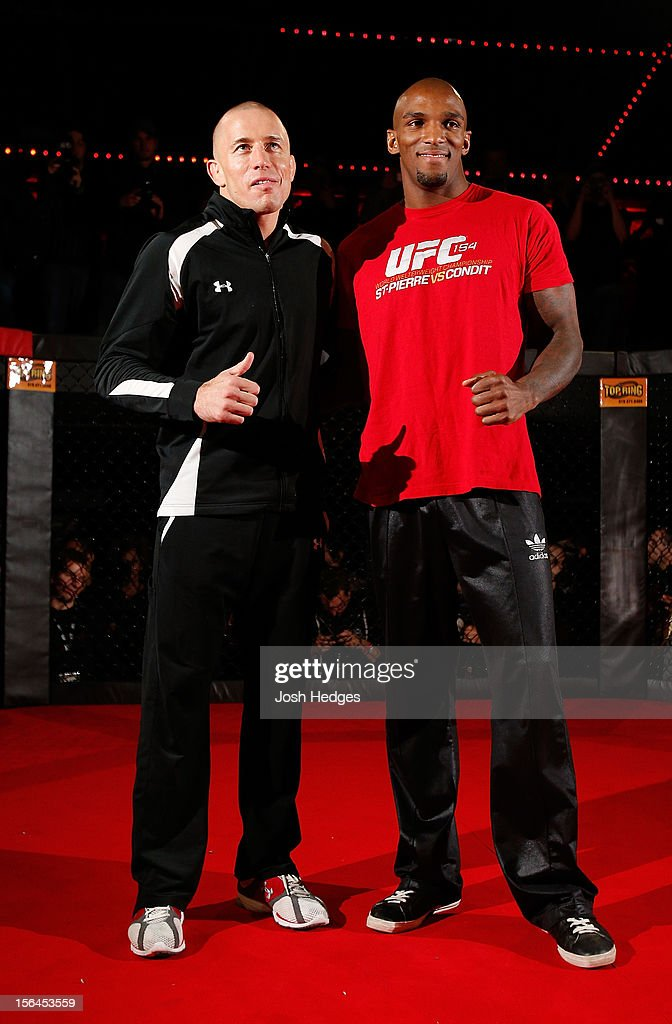 Teammates Georges St-Pierre and Francis Carmont pose for photos during an open training session ahead of UFC 154 at New City Gas on November 15, 2012 in Montreal, Quebec, Canada.