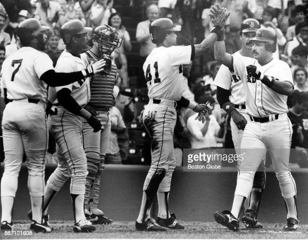 Teammates greet Boston Red Sox Tony Armas right at home plate after hitting a grand slam during a game against the Detroit Tigers at Fenway Park in...
