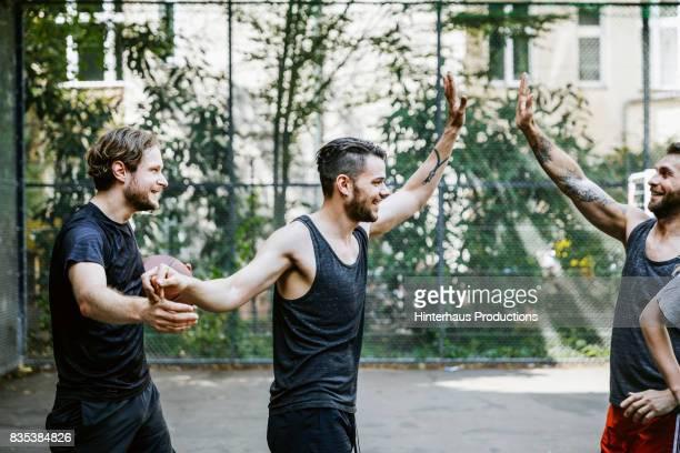 Teammates High Five, Celebrating Point Score During Basketball Game
