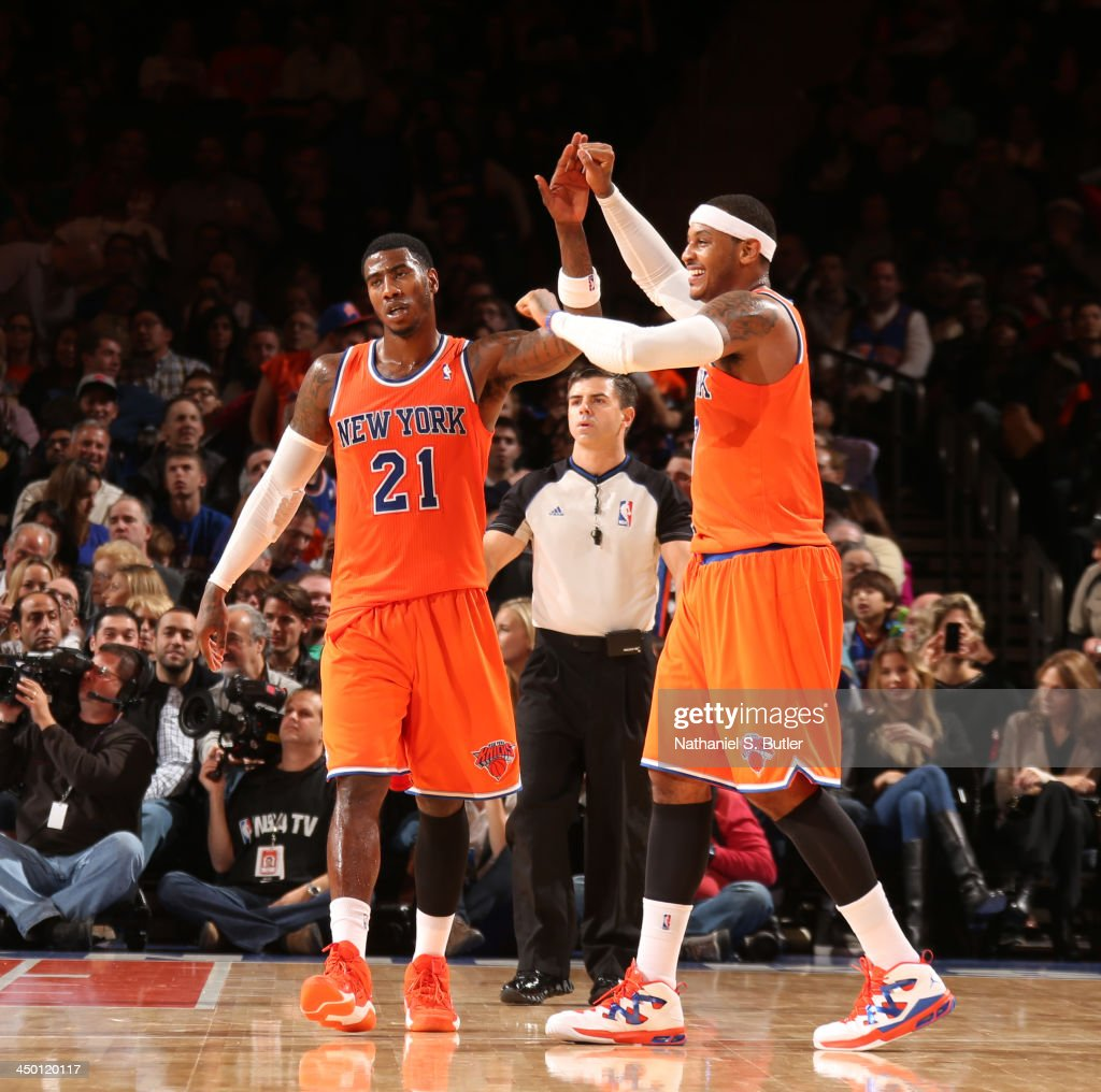 Teammates Iman Shumpert #21 of the New York Knicks and Carmelo Anthony #7 of the New York Knicks high five during a game against the Atlanta Hawks at Madison Square Garden in New York City on November 16, 2013.