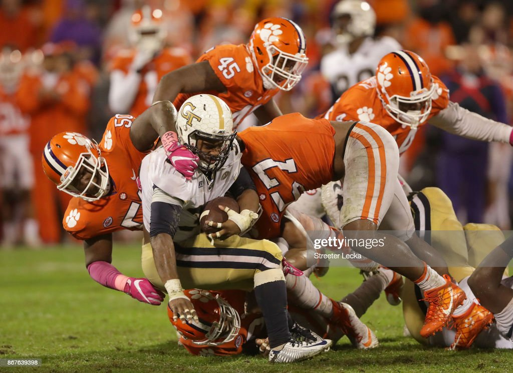 Teammates Jabril Robinson #50 and Tre Lamar #57 of the Clemson Tigers stop KirVonte Benson #30 of the Georgia Tech Yellow Jackets during their game at Memorial Stadium on October 28, 2017 in Clemson, South Carolina.