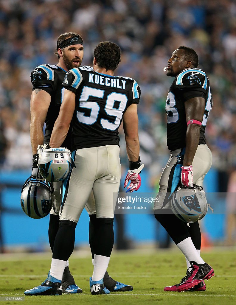 Teammates Jared Allen Luke Kuechly and Thomas Davis of the Carolina Panthers talk during a break against the Philadelphia Eagles at Bank of America...