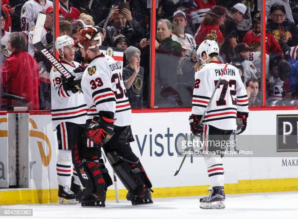 Teammates Jonathan Toews Scott Darling and Artemi Panarin of the Chicago Blackhawks celebrate their win against the Ottawa Senators at Canadian Tire...