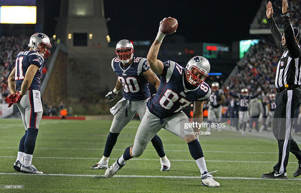 Teammates Julian Edelman (#11) and Visanthe Shinacoe (#80) watch as tight end Rob Gronkowski spikes the ball following his third quarter 24-yard touchdown pass from Tom Brady (not pictured) put New England ahead 38-17. The New England Patriots hosted the Indianapolis Colts in a regular season NFL game at Gillette Stadium.