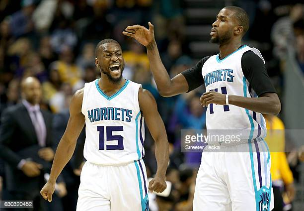Teammates Kemba Walker and Michael KiddGilchrist of the Charlotte Hornets react after play during their game against the Los Angeles Lakers at...