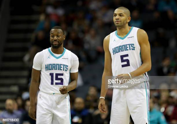 Teammates Kemba Walker and Nicolas Batum of the Charlotte Hornets watch on against the Orlando Magic during their game at Spectrum Center on December...