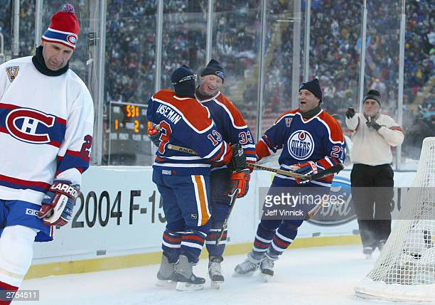 Teammates Ken Linseman Marty McSorley and Dave Semenko of the Edmonton Oilers celebrate a goal as Gaston Gingras of the Montreal Canadiens skates...
