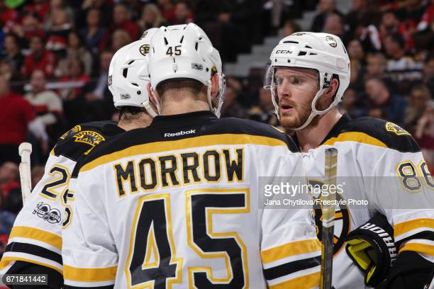 Teammates Kevan Miller Joe Morrow and Dominic Moore of the Boston Bruins chat during a stoppage in play against the Ottawa Senators in Game Five of...