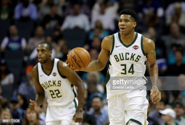Teammates Khris Middleton and Giannis Antetokounmpo of the Milwaukee Bucks go up the floor against the Charlotte Hornets during their game at...