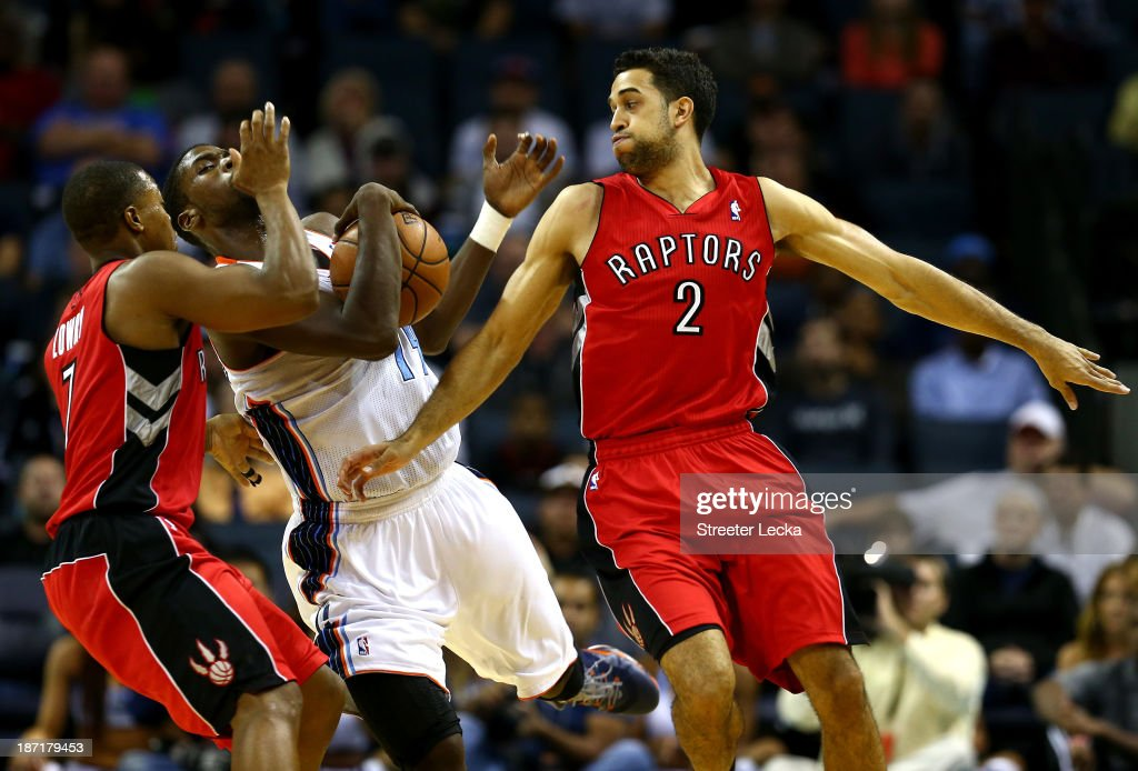 Teammates Landry Fields #2 and Kyle Lowry #7 of the Toronto Raptors run into Michael Kidd-Gilchrist #14 of the Charlotte Bobcats during their game at Time Warner Cable Arena on November 6, 2013 in Charlotte, North Carolina.