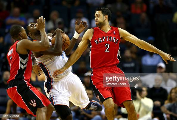 Teammates Landry Fields and Kyle Lowry of the Toronto Raptors run into Michael KiddGilchrist of the Charlotte Bobcats during their game at Time...