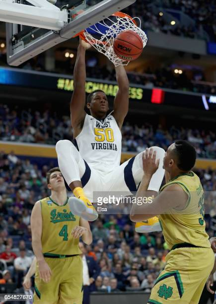 Teammates Matt Ryan and Bonzie Colson of the Notre Dame Fighting Irish watch as Sagaba Konate of the West Virginia Mountaineers dunks the ball during...