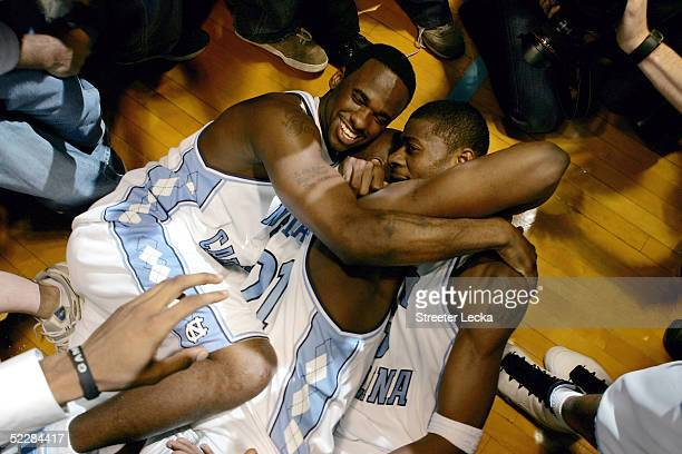 Teammates Melvin Scott Jawad Williams and Jackie Manuel of the North Carolina Tar Heels hug each other after after their victory over the Duke Blue...