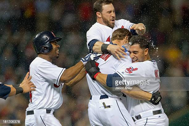 Teammates Michael Bourn Jason Kipnis and Mike Aviles celebrate with Matt Carson of the Cleveland Indians after Carson hit a walkoff RBI single during...