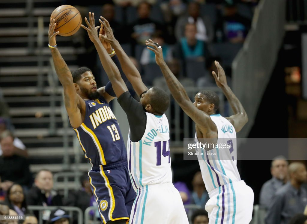 Teammates Michael Kidd-Gilchrist #14 and Marvin Williams #2 of the Charlotte Hornets try to stop Paul George #13 of the Indiana Pacers during their game at Spectrum Center on March 6, 2017 in Charlotte, North Carolina.