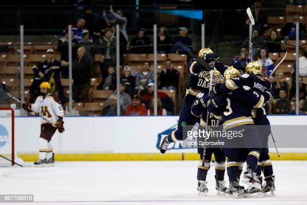 Teammates mob Notre Dame Fighting Irish right wing Anders Bjork after his second goal of the game and eventual game winner during an NCAA Northeast...