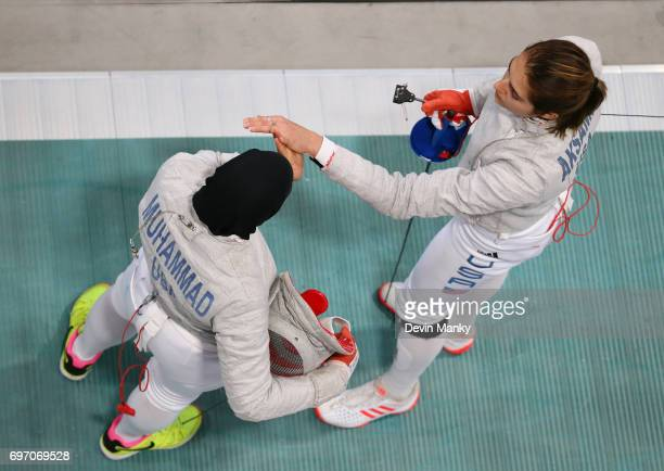 Teammates Monica Aksamit and Ibtihaj Muhammad share a highfive while switching places to fence during the Team Women's Sabre event on June 17 2017 at...