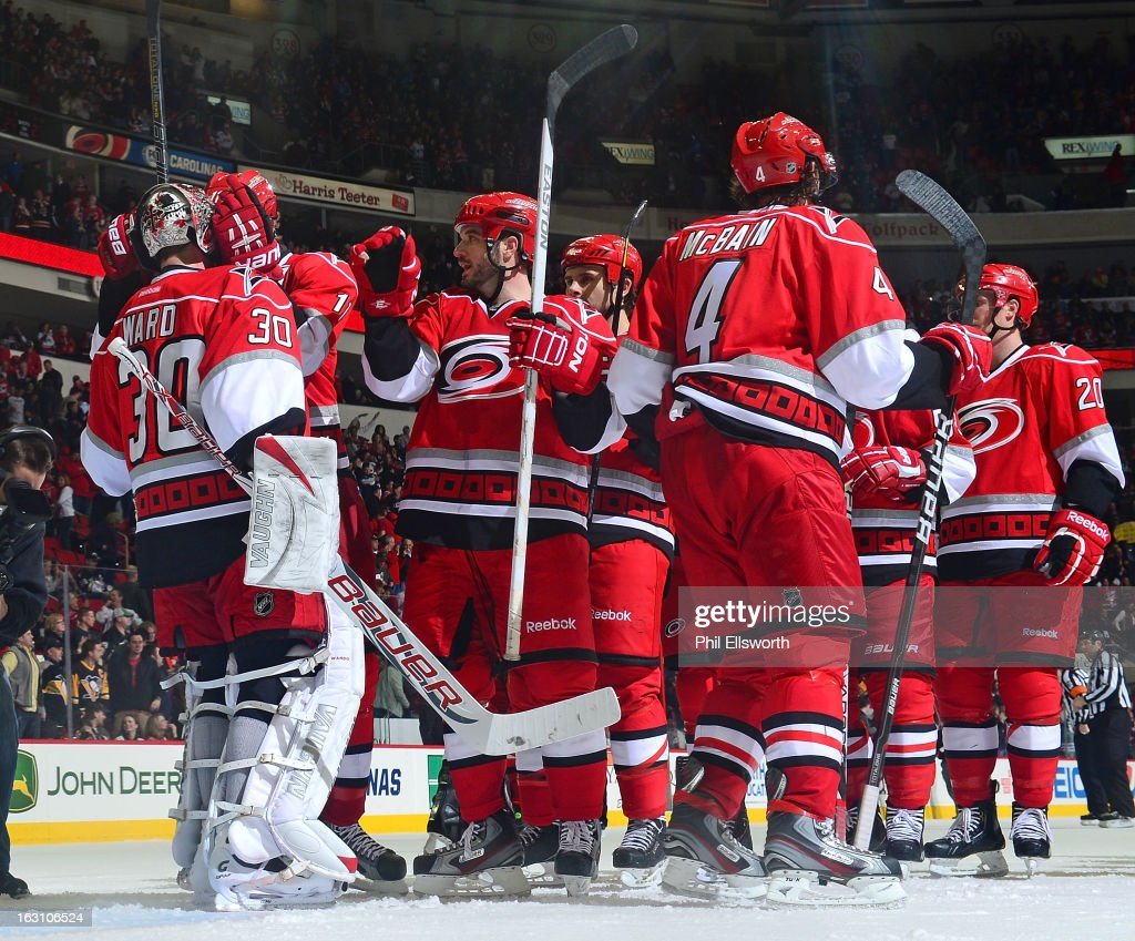 Teammates of the Carolina Hurricanes celebrate their victory over the Pittsburgh Penguins during an NHL game on February 28, 2013 at PNC Arena in Raleigh, North Carolina.