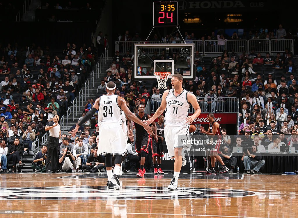 Teammates Paul Pierce #34 and Brook Lopez #11 of the Brooklyn Nets high five during a preseason game against the Miami Heat at the Barclays Center on October 17, 2013 in the Brooklyn borough of New York City.