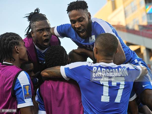 Teammates pile on Steeven Langil of Martinique after scoring a goal against Nicaragua during the second half of a CONCACAF Gold Cup Soccer match at...