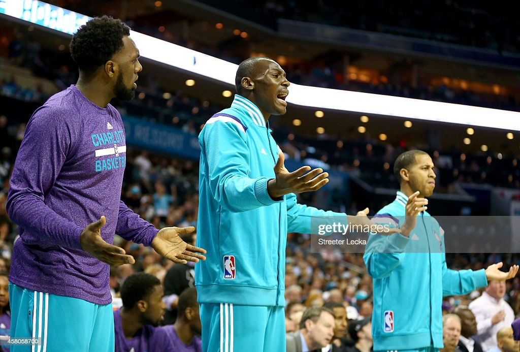 Teammates P.J. Hairston #19, Bismack Biyombo #8 and Jannero Pargo #5 of the Charlotte Hornets react to a call while on the bench during their game against the Milwaukee Bucks at Time Warner Cable Arena on October 29, 2014 in Charlotte, North Carolina.