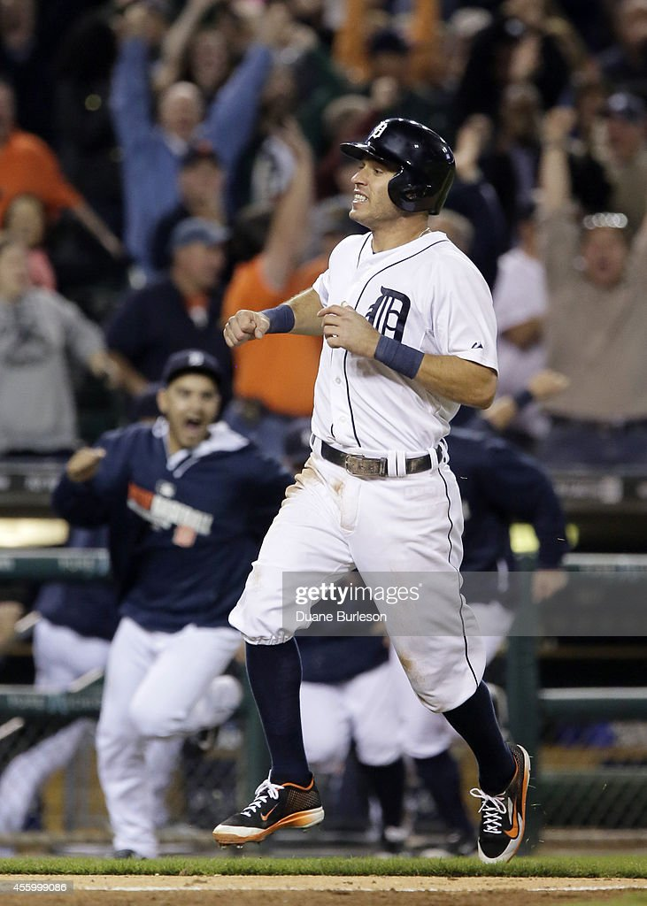 Teammates pour onto the field as <a gi-track='captionPersonalityLinkClicked' href=/galleries/search?phrase=Ian+Kinsler&family=editorial&specificpeople=538104 ng-click='$event.stopPropagation()'>Ian Kinsler</a> #3 of the Detroit Tigers scores from second base on a single by Miguel Cabrera to defeat the Chicago White Dox 4-2 in the ninth inning at Comerica Park on September 23, 2014, in Detroit, Michigan.
