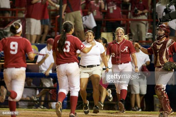 Teammates race towards pitcher Jackie Traina of the University of Alabama after her victory against the University of Oklahoma during the Division I...