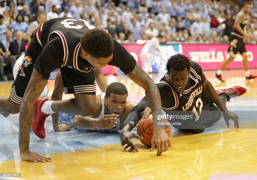 Teammates Ray Spalding #13 and Mangok Mathiang #12 of the Louisville Cardinals dive after a loose ball against Kennedy Meeks #3 of the North Carolina Tar Heels during their game at the Dean Smith Center on February 22, 2017 in Chapel Hill, North Carolina.