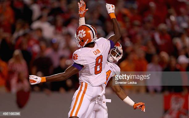 Teammates RayRay McCloud of the Clemson Tigers and Deon Cain of the Clemson Tigers celebrate after McCloud makes a touchdown catch against the North...